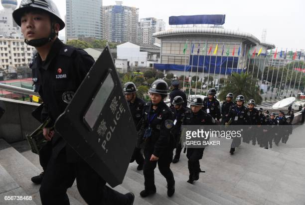 Chinese police with riot shields march up the steps of the Helong stadium before the World Cup football qualifying match between China and South...
