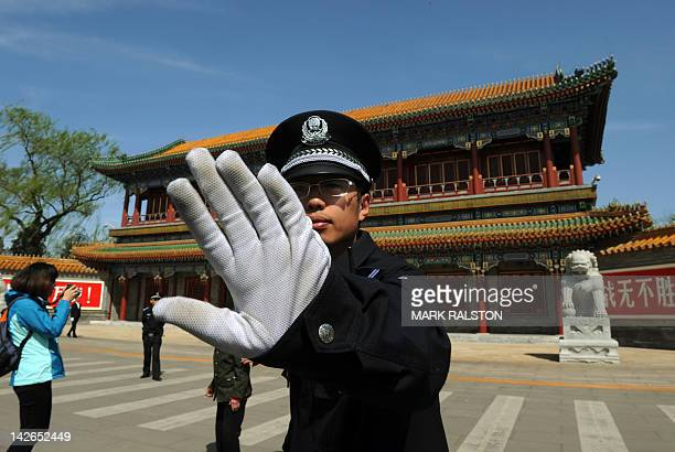 A Chinese policeman blocks photos being taken outside Zhongnanhai which serves as the central headquarters for the Communist Party of China after the...