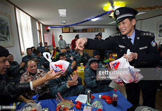 A Chinese policeman hands out food items to foreign inmates before an evening held to celebrate Christmas at the Shanghai Qingpu Prison December 24...