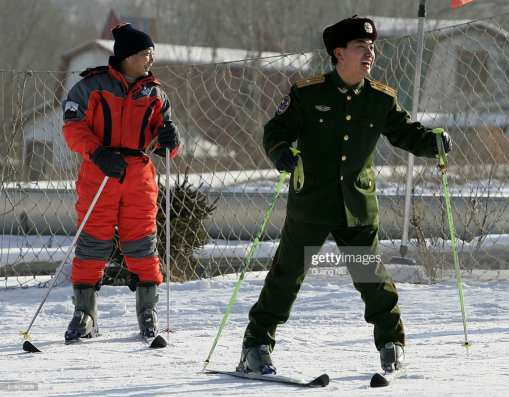 A Chinese policeman (R) laughs at a skiing resort on January 7, 2005 in Harbin, China. Local authorities are preparing to bid for the 2014 Winter Olympic Games despite losing the bid to host the 2010 winter games.