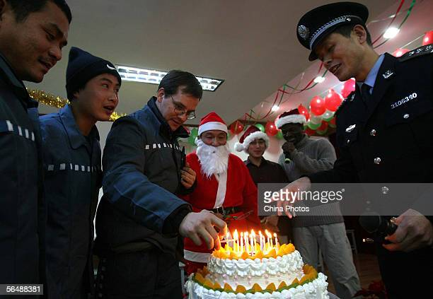 A Chinese policeman lights candles with foreign inmates during an evening held to celebrate Christmas at the Shanghai Qingpu Prison December 24 2005...