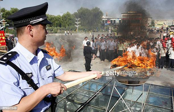 A Chinese policeman lits a cauldron filled with illicit drugs during a ceremony to mark the UN's International Day Against Drug Abuse and Illicit...