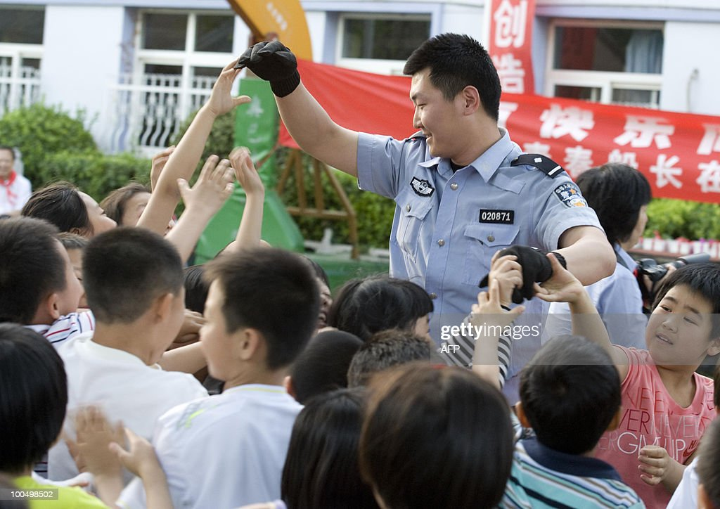 A Chinese policeman meets the school children during a safety demonstration at an elementary school in Beijing on May 24, 2010. Beijing police are recruiting parents to join patrols of school grounds as cities nationwide beef up security following a spate of attacks on children. CHINA