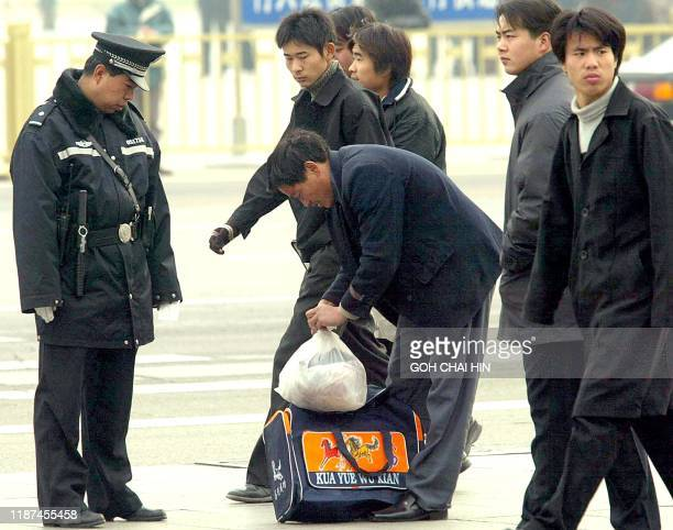 A Chinese policeman orders a passerby to empty his bag outside the main entrance to the Great Hall of the People in Beijing 10 November 2002 When...