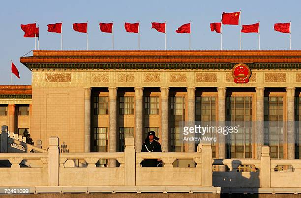 Chinese policeman stands guard in front of the Great Hall of the People during sunrise before the opening session of the National People's Congress,...