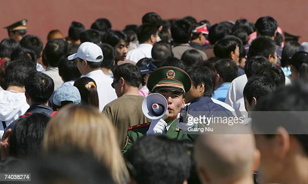 Chinese policeman tries to control crowds as thousands of people visit Tiananmen Square to mark May Day on May 1 2007 in Beijing China 50 people were...