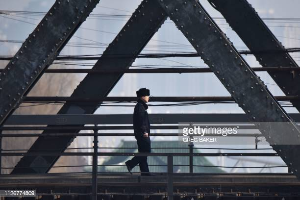 Chinese policeman walks on the Sino-Korean Friendship Bridge, which spans the Yalu River between China and North Korea, in the border city of...