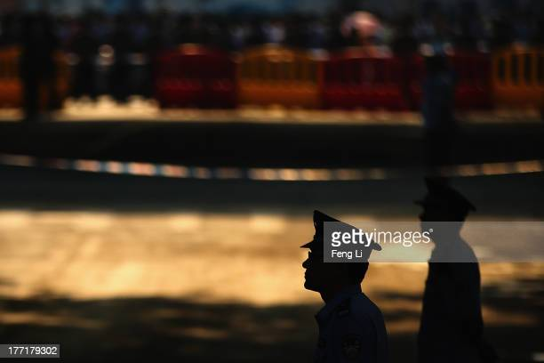 Chinese policemen guard outside the Jinan Intermediate People's Court on August 22 2013 in Jinan China Former Chinese politician Bo Xilai is standing...