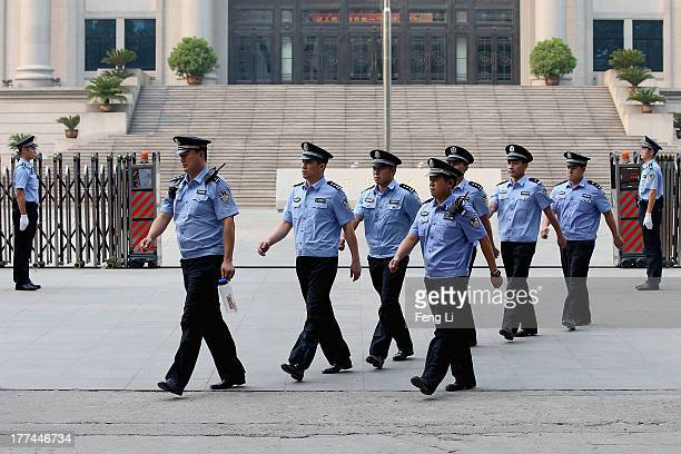 Chinese policemen guard outside the Jinan Intermediate People's Court on August 23 2013 in Jinan China Ousted Chinese politician Bo Xilai is standing...