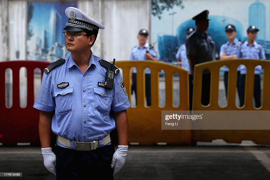 Chinese policemen guard outside the Jinan Intermediate People's Court during the fourth day of former Chinese politician Bo Xilai's trial on August 25, 2013 in Jinan, China. Ousted Chinese politician Bo Xilai is standing trial on charges of bribery, corruption and abuse of power for a third day. Bo Xilai made global headlines last year when his wife Gu Kailai was charged and convicted of murdering British businessman Neil Heywood.