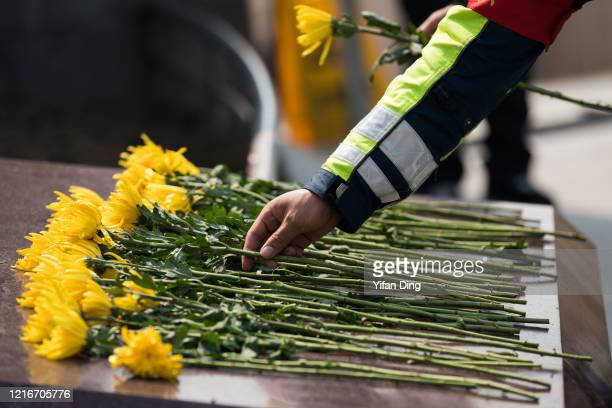 Chinese policemen lay flowers during a memorial to mourn for victims of COVID-19 at Shanghai People's Heros Memorial Tower on April 04, 2020 in...