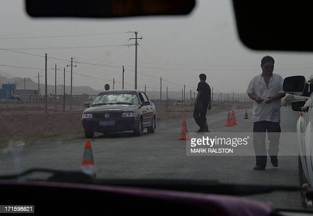 Chinese policemen man a roadblock leading into the riot affected town of Lukqun Xinjiang Province on June 27 2013 Riots in China's ethnically divided...