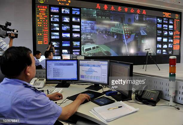 Chinese policemen watch screens showing public areas monitored by security cameras in Urumqi northwest China's Xinjiang region on July 1 2010 Police...