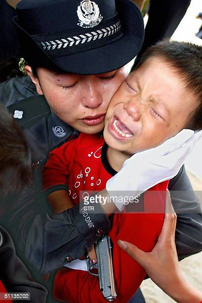 Chinese policewoman consoles one of the children rescued from traffickers as a group of 18 kidnapped toddlers arrived back in Kunming southwest...