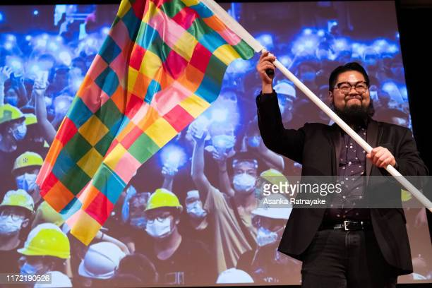 Chinese political cartoonist Badiucao waves a flag he created inspired by the Lenon Wall in Hong Kong during the Be Water: Hong Kong v China event at...