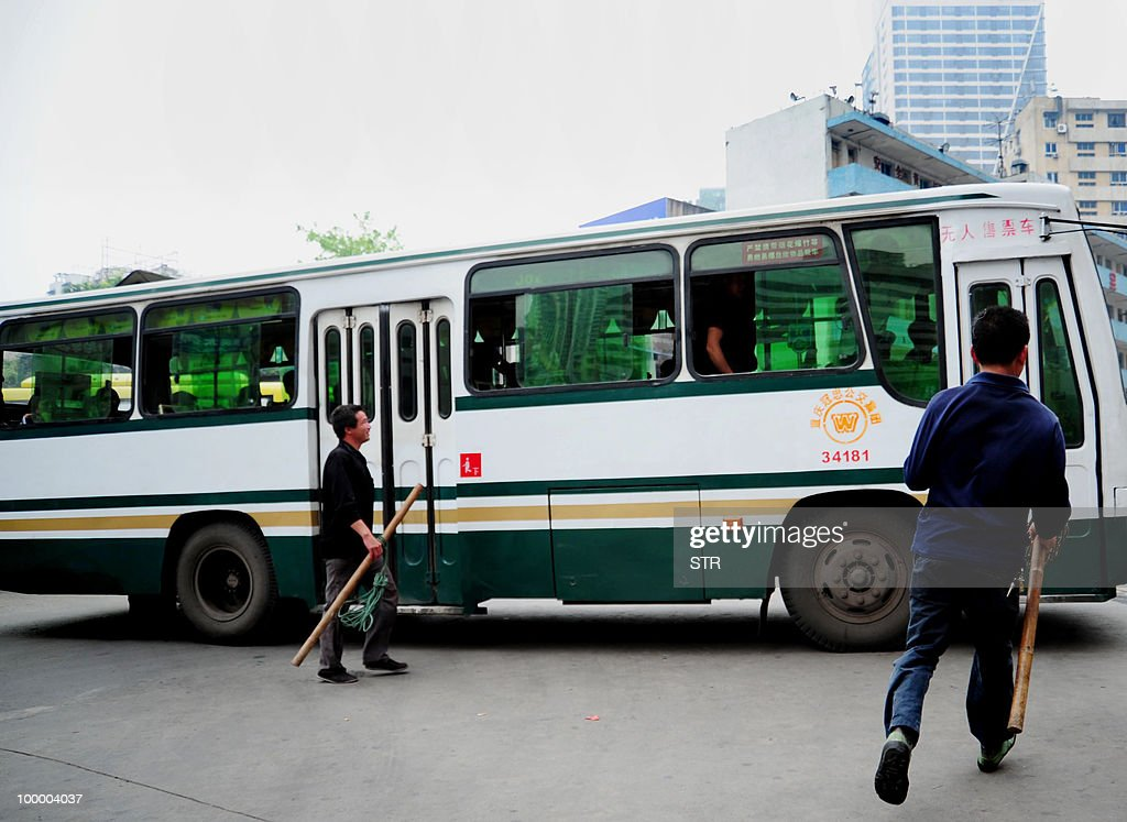 Chinese porter, also known as a 'Bang Bang' in the local dialect refering to the way they carry goods, run towards a bus carrying potential customers of their services, on May 19, 2010 along a road in southwest China's mountainous Chongqing municipality. The 'Bang Bang', who are generally migrants from rural areaswith a population of around 400,000 persons, are a common sight in Chongqing. The overall improvement of their living conditions and other migrant workers' lives is still a big challenge for the municipal government. CHINA