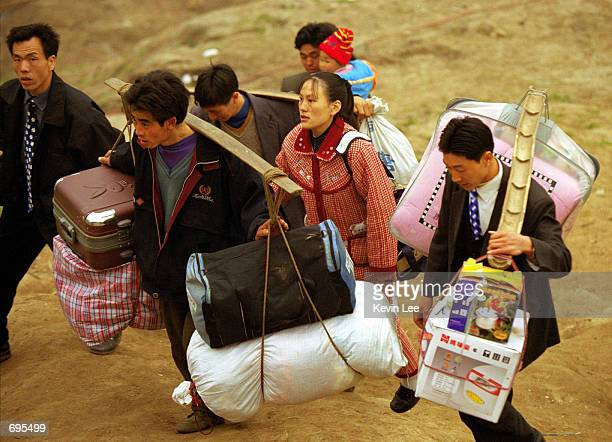 Chinese porters carry luggage for passengers arriving from a ferry heading toward their hometowns February 7 2002 in Feng Jie a coastal city on...
