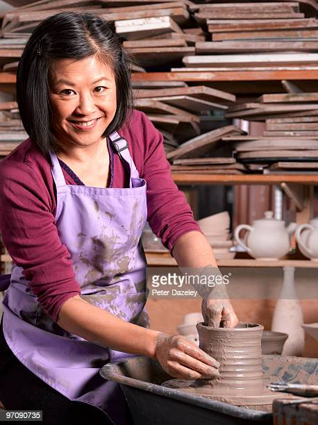 chinese potter throwing vase at potters wheel