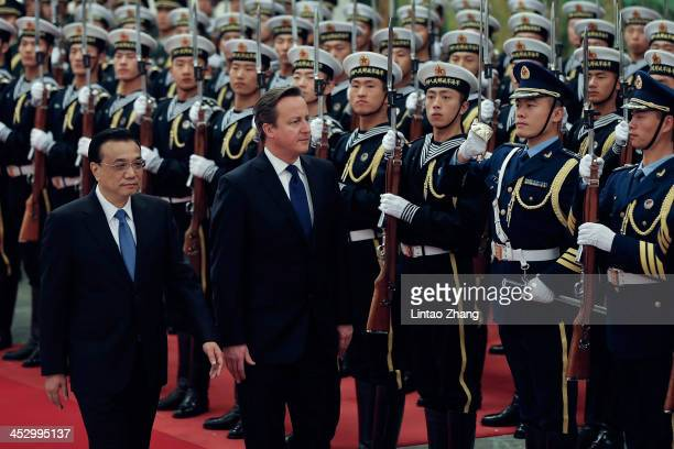Chinese Premier Li Keqiang accompanies British Prime Minister David Cameron to view an honour guard during a welcoming ceremony inside the Great Hall...