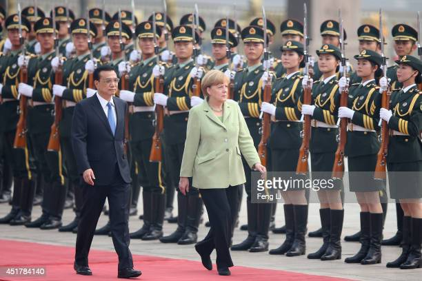 Chinese Premier Li Keqiang accompanies German Chancellor Angela Merkel to view an honour guard during a welcoming ceremony outside the Great Hall of...