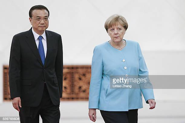 Chinese Premier Li Keqiang accompanies German Chancellor Angela Merkel to view an honour guard during a welcoming ceremony at the Great Hall of the...
