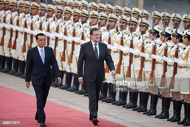 Chinese Premier Li Keqiang accompanies Spanish Prime Minister Mariano Rajoy to view an honour guard during a welcoming ceremony outside the Great...