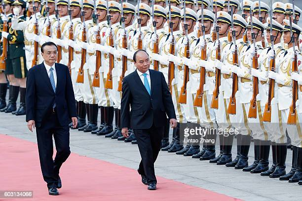 Chinese Premier Li Keqiang accompanies Vietnamese Prime Minister Nguyen Xuan Phuc to view an honour guard during a welcoming ceremony outside the...