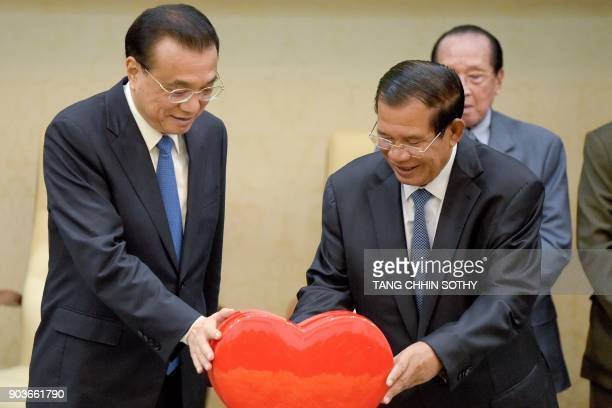 Chinese Premier Li Keqiang and Cambodian Prime Minister Hun Sen hold a heart symbol during a signing ceremony at the Peace Palace in Phnom Penh on...