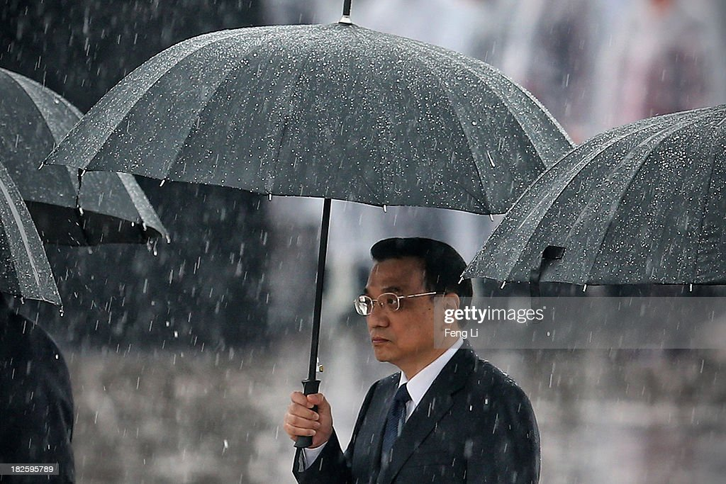 Chinese Premier Li Keqiang and Chinese Communist Party top leaders hold their umbrellas in the rain as they walk to the Monument to the People's Heroes during a ceremony marking the 64th anniversary of the founding of the People's Republic of China at Tiananmen Square on October 1, 2013 in Beijing, China. On October 1, 1949, Chinese leader Mao Zedong stood at the Tiananmen Rostrum to declare the founding of the People's Republic of China.