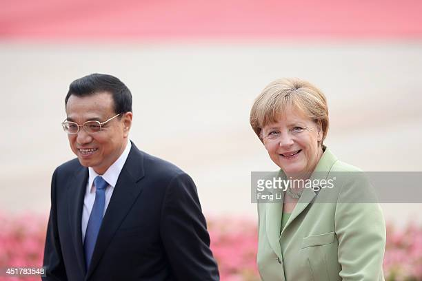 Chinese Premier Li Keqiang and German Chancellor Angela Merkel talk after viewing an honour guard during a welcoming ceremony outside the Great Hall...