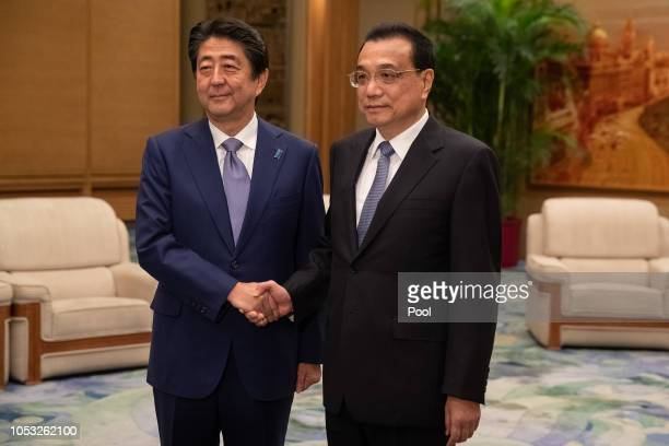Chinese Premier Li Keqiang and Japanese Prime Minister Shinzo Abe shake hands during their meeting at the Great Hall of the People on October 25,...