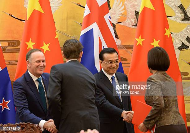 Chinese Premier Li Keqiang and New Zealand Prime Minister John Key attend a signing ceremony at the Great Hall of the People in Beijing on April 18...