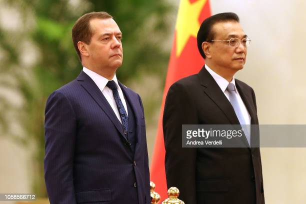 Chinese Premier Li Keqiang and Russian Prime Minister Dmitry Medvedev listen to their national anthems during the welcoming ceremony at The Great...