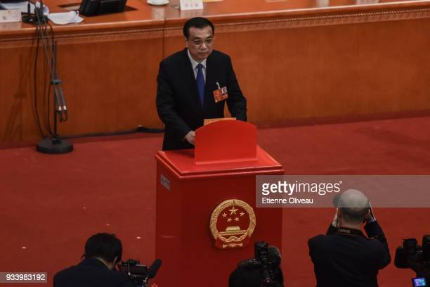 Chinese Premier Li Keqiang casts his vote during the seventh plenary session of the 13th National People's Congress at the Great Hall of the People...