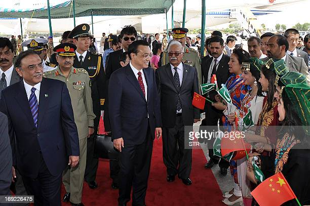 Chinese Premier Li Keqiang , flanked by Pakistani President Asif Ali Zardari and caretaker premier Mir Hazar Khan Khoso is welcomed by hostesses...