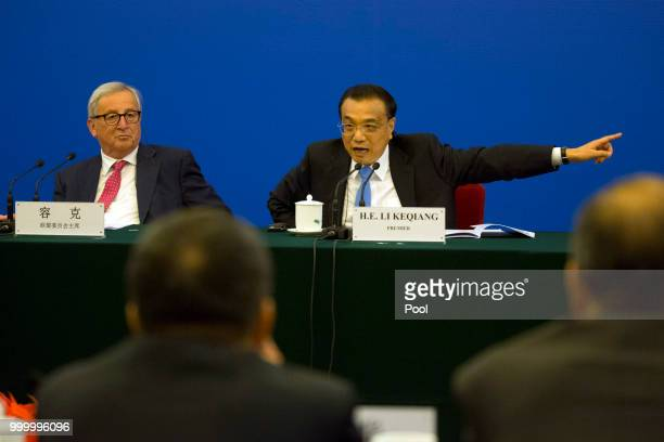 Chinese Premier Li Keqiang gestures as he calls for action to problems raised by European businessmen near European Commission President JeanClaude...