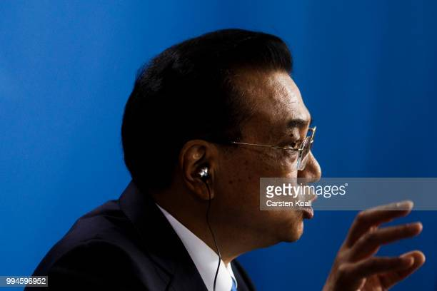 Chinese Premier Li Keqiang gestures speaks to the media together with German Chancellor Angela Merkel following Germany-China government...