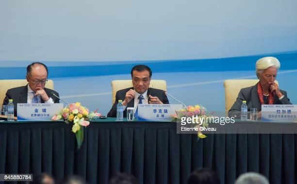 Chinese Premier Li Keqiang holds his glasses as he sits between President Jim Yong Kim of the World Bank and Managing Director Christine Lagarde of...