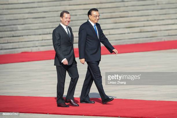 Chinese Premier Li Keqiang invites Russia's Prime Minister Dmitry Medvedev to view an honour guard during a welcoming ceremony outside the Great Hall...