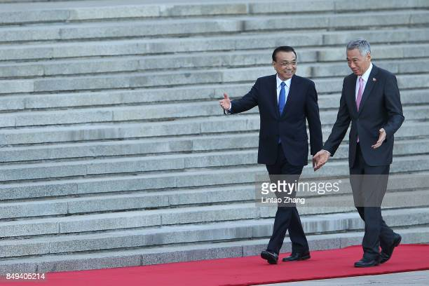 Chinese Premier Li Keqiang invites Singapore Prime Minister Lee Hsien Loong to view a guard of honour during a welcoming ceremony outside the Great...