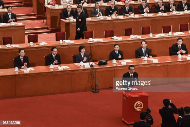 Chinese Premier Li Keqiang poses for a picture as Chinese President Xi Jinping reaches his seat after they casted their ballots during the sixth...