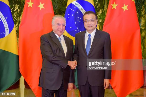 Chinese Premier Li Keqiang shakes hands with Brazil President Michel Temer in Beijing on September 1, 2017. / AFP PHOTO / POOL / Etienne Oliveau