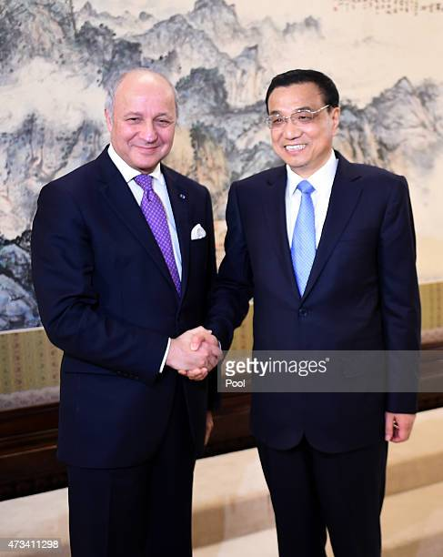 Chinese Premier Li Keqiang shakes hands with French Foreign Minister Laurent Fabius during a meeting at the Zhongnanhai leadership compound on May...