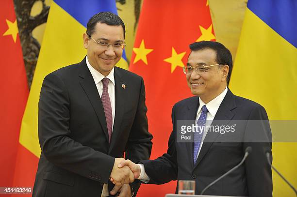 Chinese Premier Li Keqiang shakes hands with Romanian Prime Minister Victor Ponta after a joint news conference at the Great Hall of the People on...