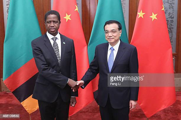 Chinese Premier Li Keqiang shakes hands with Zambia's President Edgar Chagwa Lungu at the Great Hall of the People on March 30 2015 in Beijing China