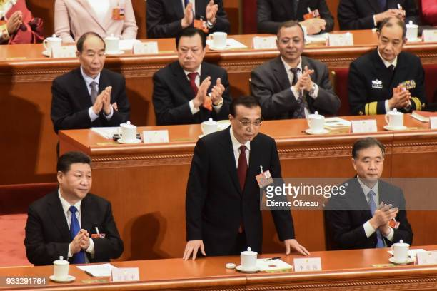 Chinese Premier Li Keqiang sits down after swearing an oath during the sixth plenary session of the National People's Congress at the Great Hall of...