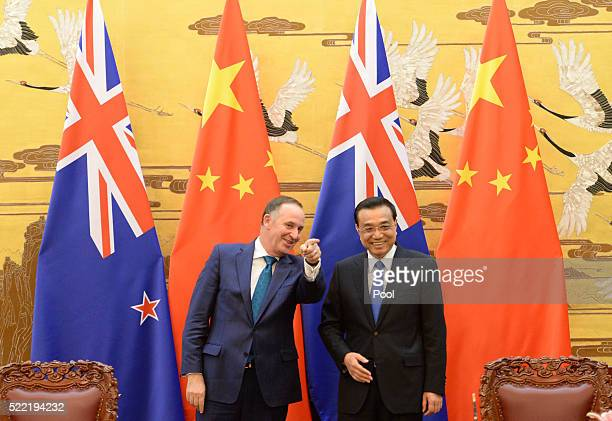 Chinese Premier Li Keqiang speaks with New Zealand Prime Minister John Key during a signing ceremony at the Great Hall of the People on April 18 2016...