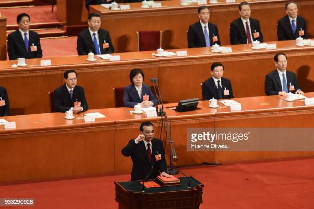 Chinese Premier Li Keqiang swears an oath after being elected to a second term as Chinese President Xi Jinping watches during the sixth plenary...