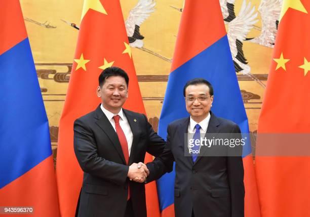 Chinese Premier Li Keqiang talks to Malaysia's new government advisor Daim Zainuddin during their meeting at the Zhongnanhai Leadership Compound on...