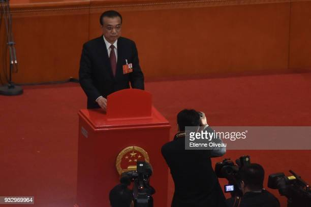 Chinese Premier Li Keqiang votes during the 5th plenary session of the first session of the 13th National People's Congress at the Great Hall of the...